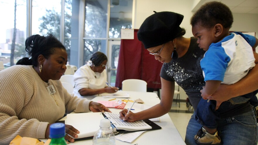 Charnisha Thomas signs in during the Louisiana presidential primary in 2008. In a new poll released Monday, African-American voters say they wait in longer lines and travel farther to get to polling places than white voters.