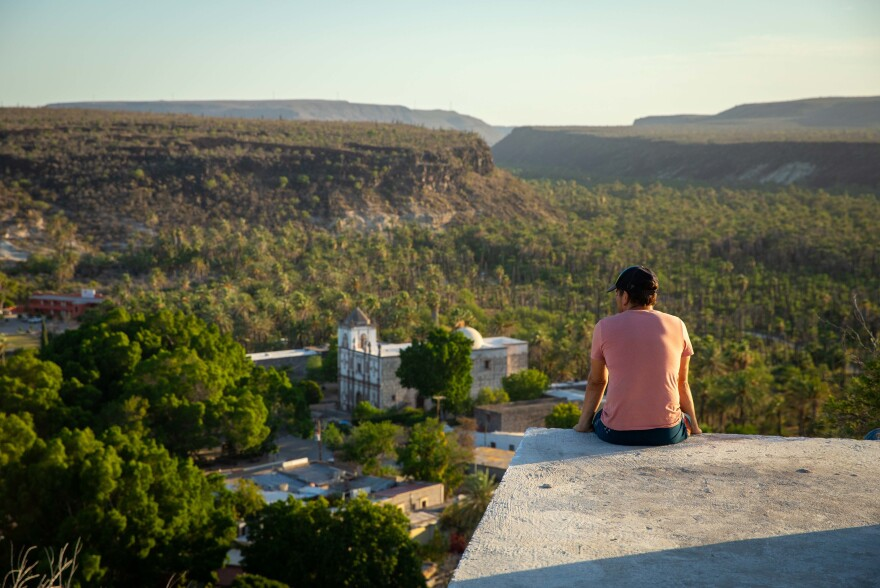 After a hike up to the local water tower, Hiro looks out over the downtown plaza and mission of San Ignacio. His family has been here for generations and were some of the first immigrants to the area following the building of the mission.