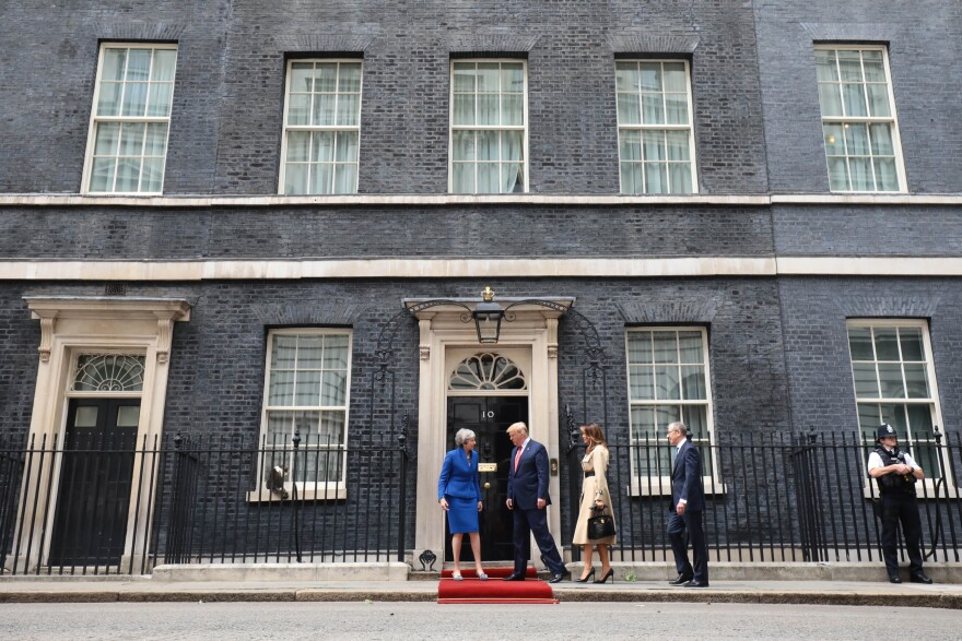 May, Trump, first lady Melania Trump and Philip May arrive at 10 Downing Street, the prime minister's residence, where a red carpet was rolled out to greet them. On a windowsill to the left, Chief Mouser Larry the Cat keeps watch.