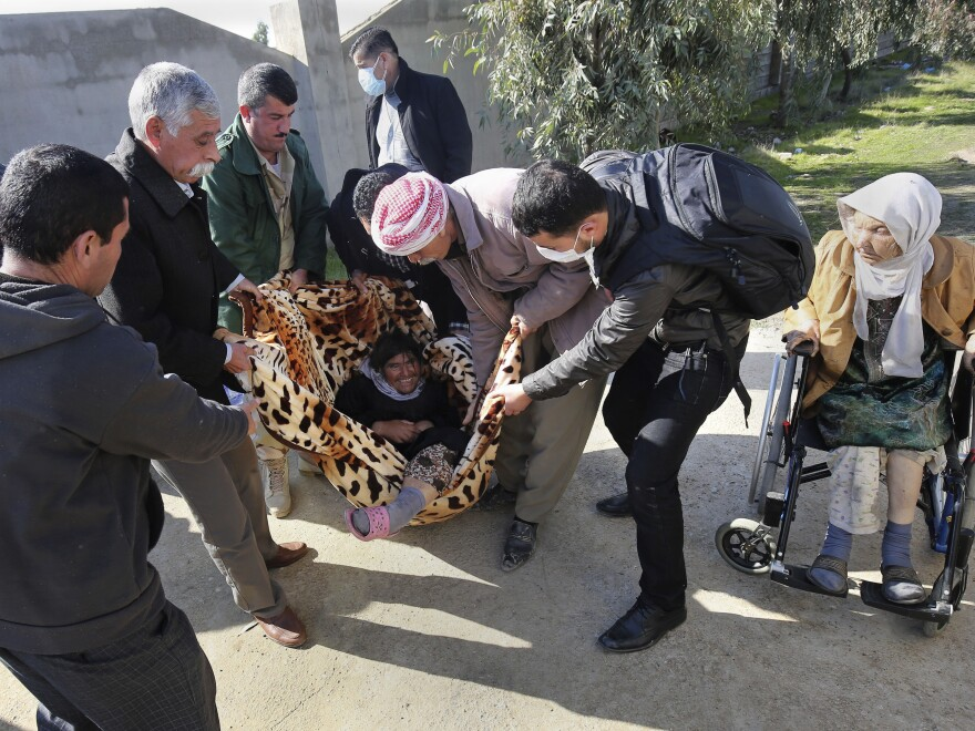 A mentally disabled Yazidi man is carried to a bus that will bring him to the Kurdish city of Dohuk, after being released by Islamic militants, in Alton Kupri, outside Kirkuk, Iraq, on Sunday.