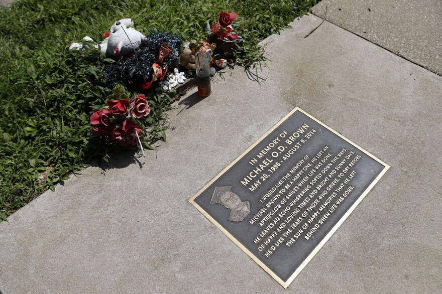 In this July 25, 2019, photo, flowers and other items lay near a memorial plaque in the sidewalk near the spot where Michael Brown was shot and killed by a police officer five years ago in Ferguson, Mo. (Jeff Roberson/AP)
