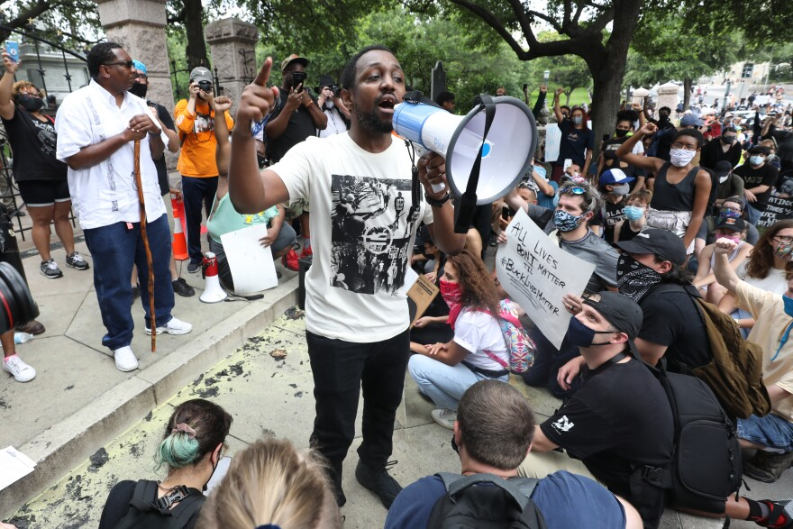 Chas Moore, founder and executive director of the racial justice group the Austin Justice Coalition, speaks to a crowd at the Capitol on Sunday during a rally protesting police violence against black people.