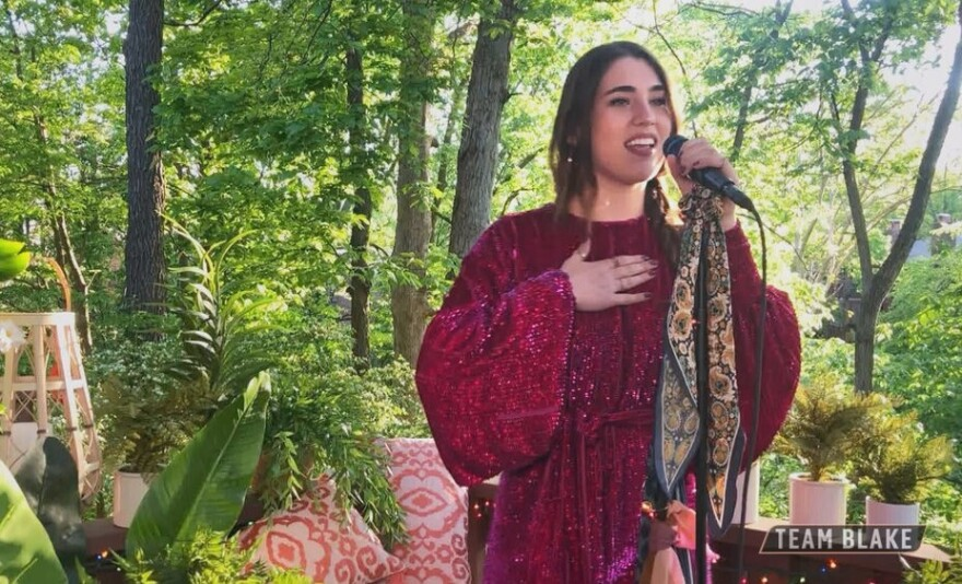 """Joanna Serenko sings the Bill Withers classic """"Lean on Me"""" in her Kirkwood-home backyard during the Top 9 Performances on The Voice singing competition."""