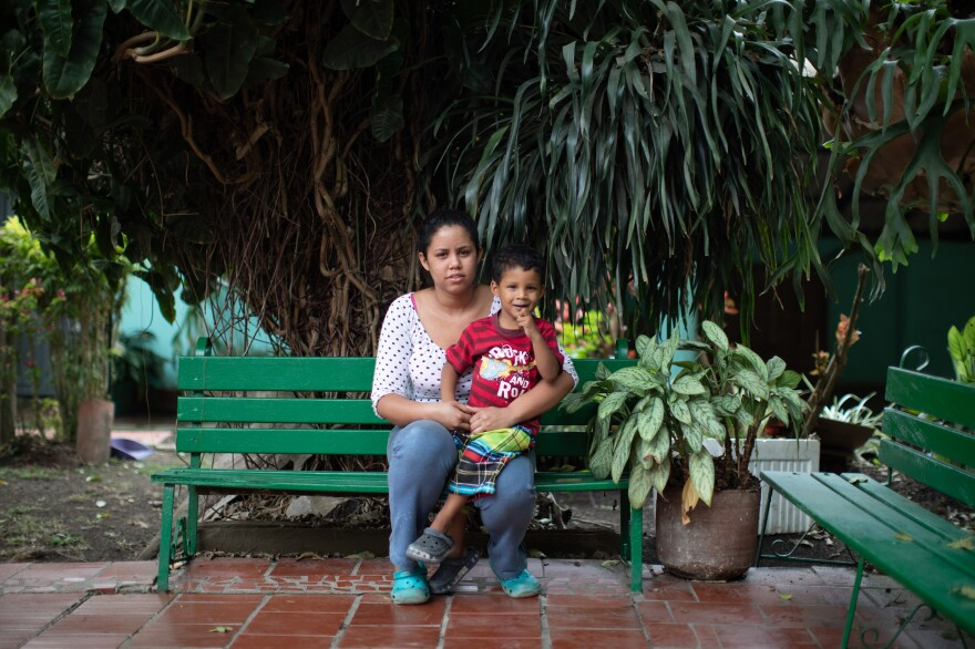 Jennifer Guanipa sits with her son. She prepares meals for migrants in a shelter in Curití, south of Bucaramanga, Colombia, in exchange for a place for her family to stay.