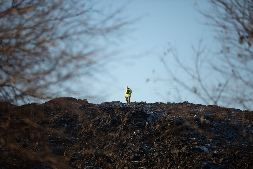 A person wearing construction gear stands on top of the six-story pile of shingles known as Shingle Mountain. They work with Modern Geoscientists, an environmental company and is inspects the air quality during the removal process to make sure the air is not harmful to the residents.