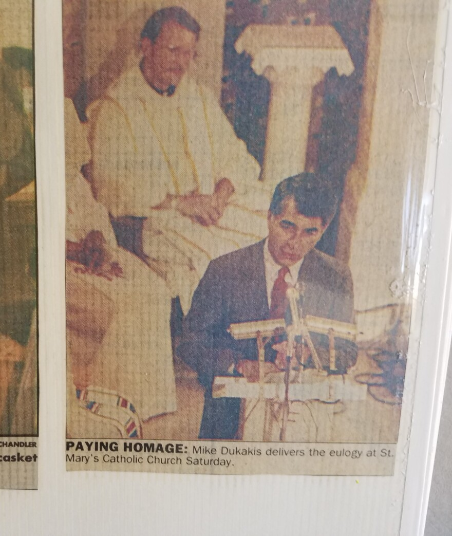 Newspaper clipping of Massachusetts Gov. Michael Dukakis delivering the eulogy at Willie Velásquez's funeral, 1988.