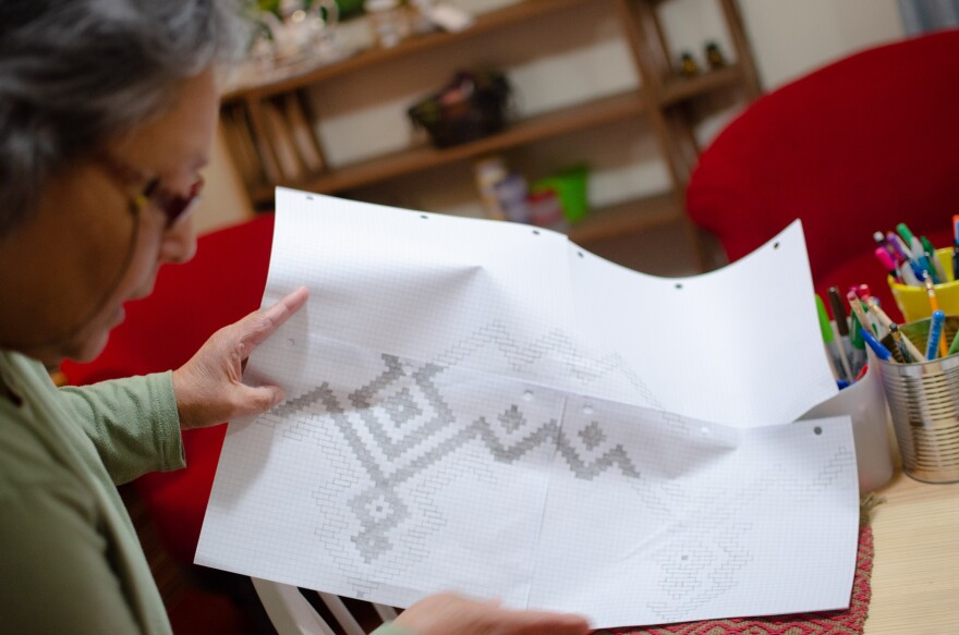 Betty Maney studies a recent pattern she sketched out on graph paper.