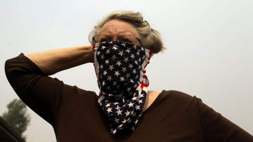 Kay Dyson covers her face to protect from smoke in Springerville, Ariz., earlier today (June 8, 2011).