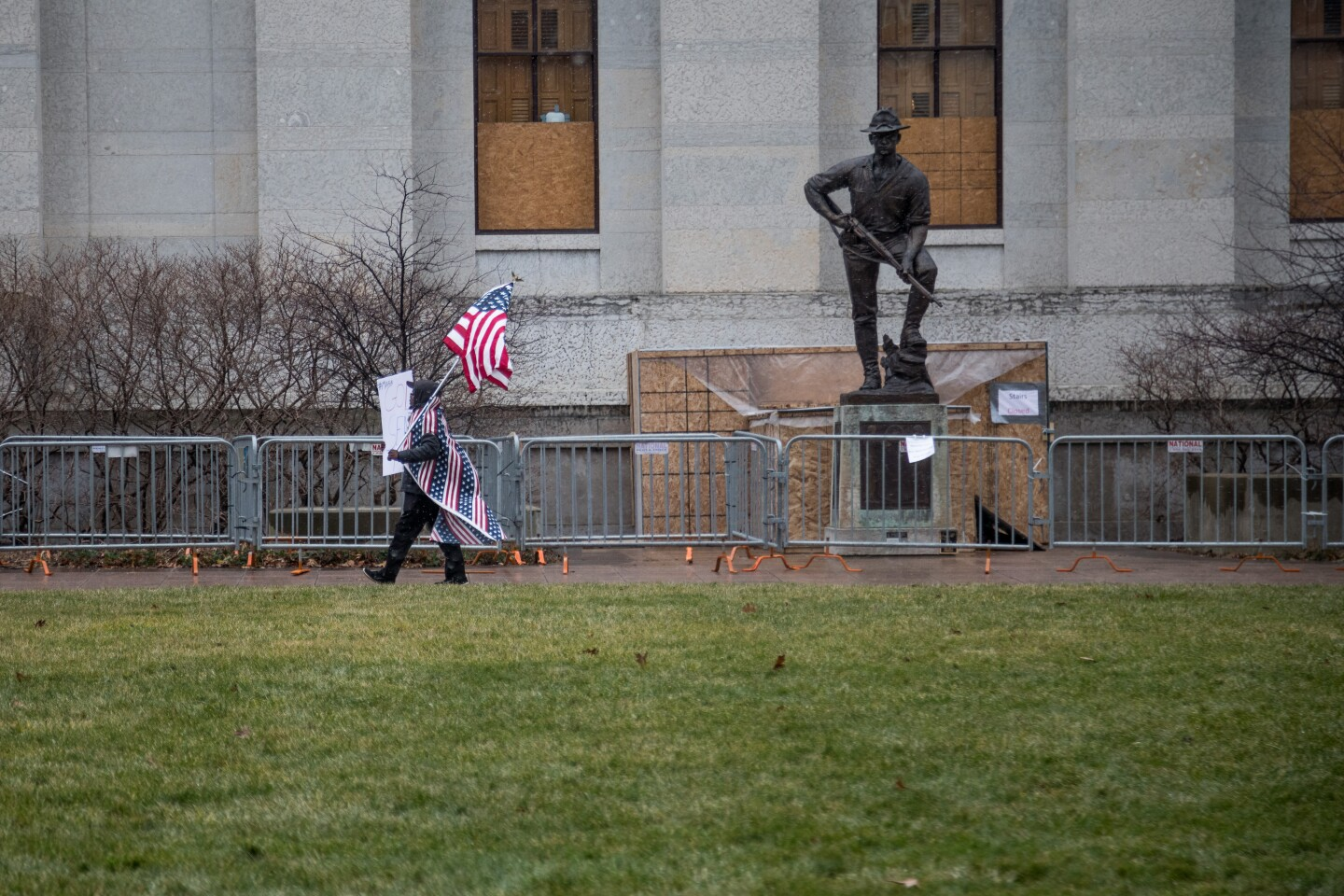 A right wing demonstrator walks past a WWI monument in front of the Ohio Statehouse during a planned Boogaloo Bois Demonstration, Ohio State Capitol, Columbus, Ohio. Sunday, Jan. 17, 2021