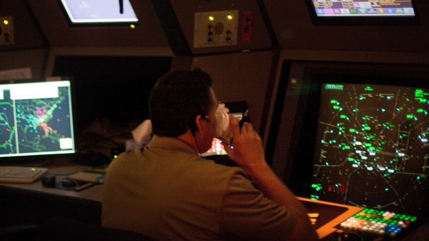 An air traffic controller drinks a cup of coffee while working in a terminal radar approach control room Monday at the Atlanta TRACON in Peachtree City, Ga. Several recent reports of controllers nodding off on the job prompted new scheduling rules.