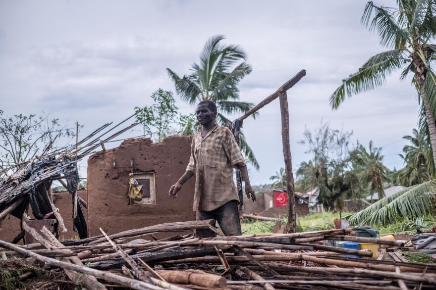 A man stands in his wrecked home in Macomia.