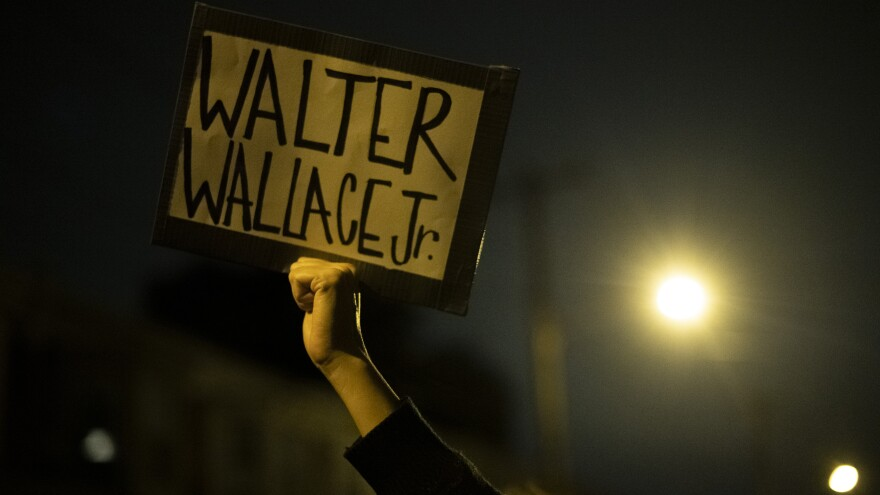 "PHILADELPHIA, PA - OCTOBER 27: A demonstrator holds a placard reading ""WALTER WALLACE JR."" during a protest near the location where Walter Wallace, Jr. was killed by two police officers on October 27, 2020 in Philadelphia. (Photo by Mark Makela/Getty Images)"