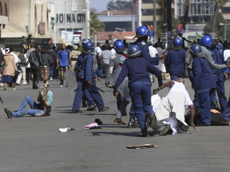 Riot police arrest and forcibly apprehend protesters during protests in Harare on Friday.
