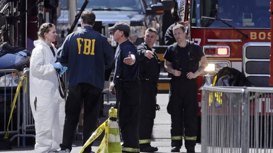 Boston firefighters talk with FBI agents and a crime scene photographer Tuesday at the scene of the Boston Marathon explosions.