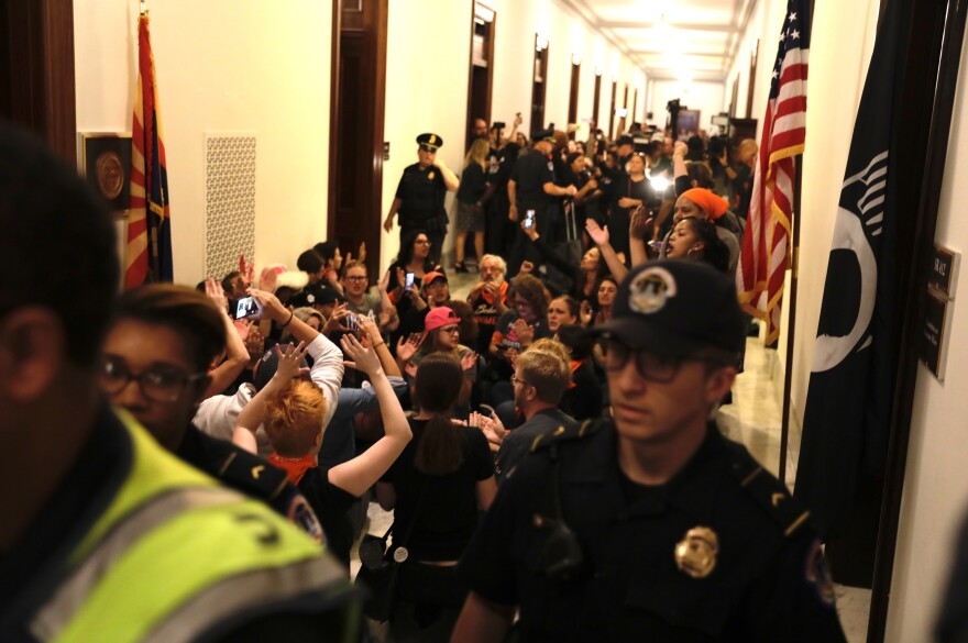 Protesters gather outside Flake's office, not long after the Republican voted to advance Brett Kavanaugh's nomination. Flake's was not the only office visited by demonstrators Friday. Other senators who had been considered on the fence also saw last-minute lobbying.
