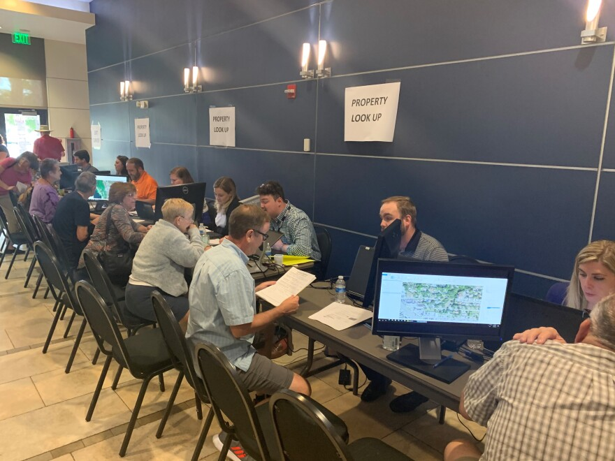 People sit at a line of computers to learn about property risk