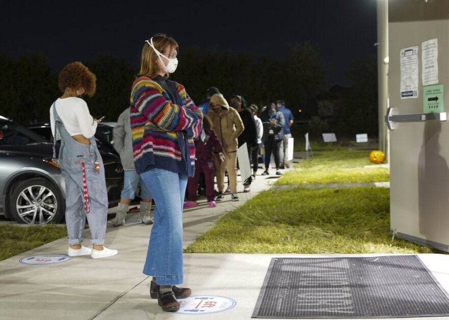 A woman waits outside a 24-hour polling station in Houston, as a line forms behind her on the sidewalk.