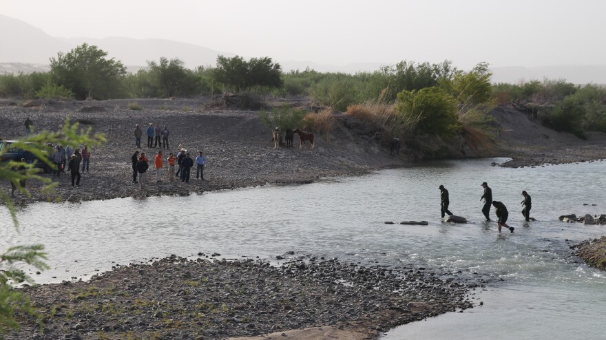 Four senior U.S. Border Patrol agents cross the Rio Grande at Big Bend National Park, Texas, as a crowd gathers to greet them on the Mexican side.