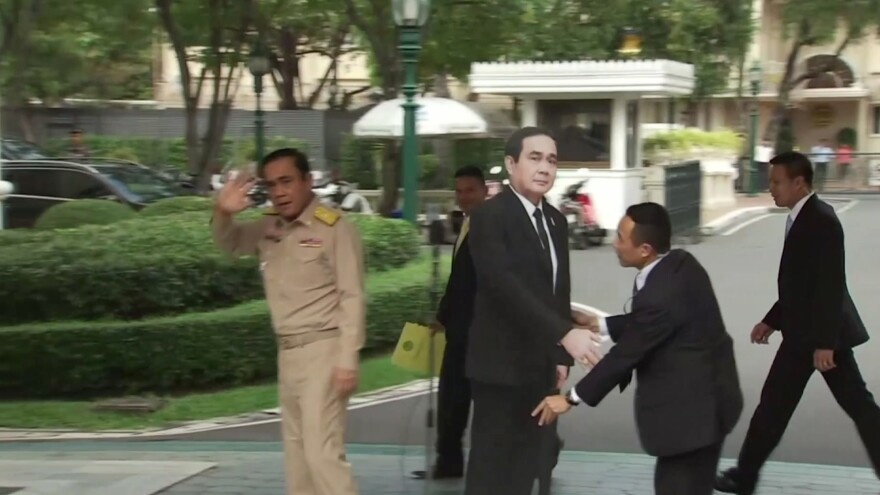 In this image from video, Thailand's Prime Minister Prayuth Chan-ocha (left) waves and walks off as a life-sized cardboard cut-out figure of himself is placed next to the microphone during a media conference in Bangkok on Monday.