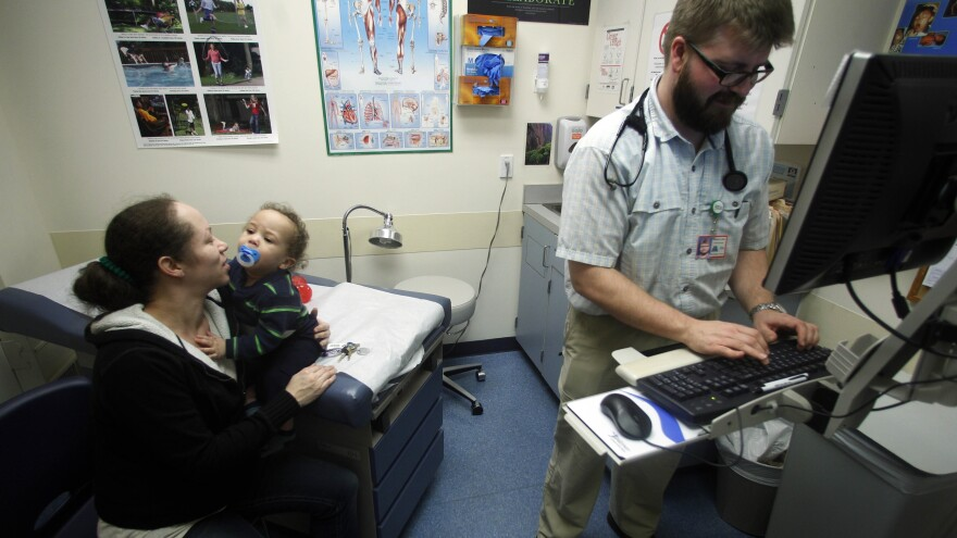 Kesha Wilson holds her 1-year-old son, Kamiyan Cooper, while family nurse practitioner Terrance James makes notes as part of an examination, at a county health center in Portland, Ore., in 2012.