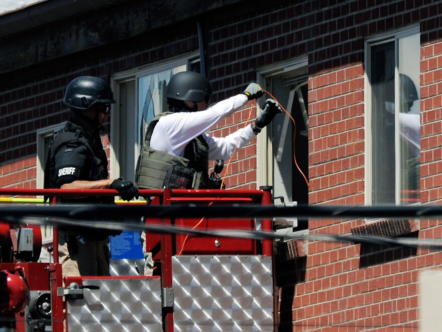Law enforcement officers prepare to disarm the suspect's booby-trapped apartment Friday.