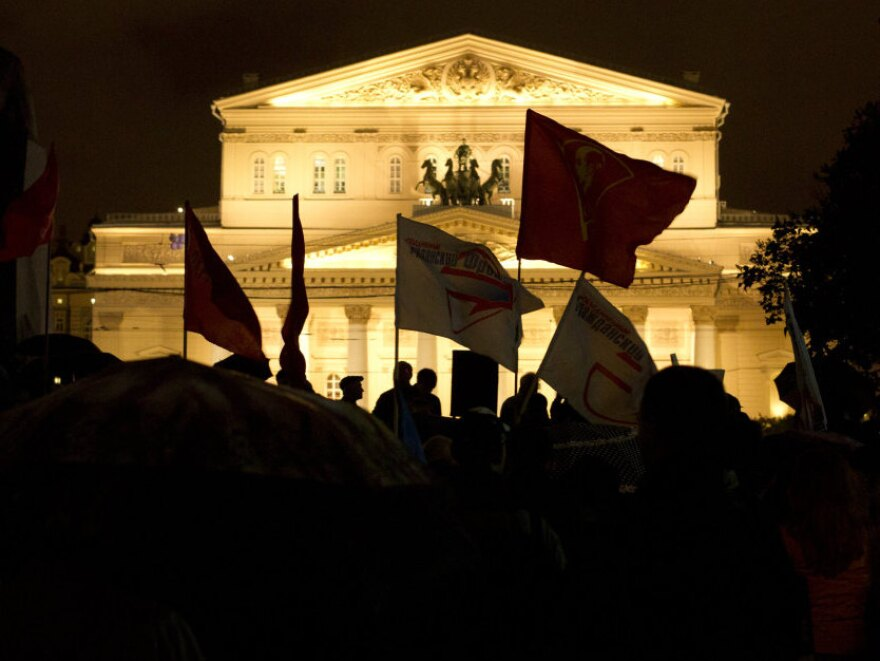 <p>Opposition supporters hold a rally Wednesday in Moscow, with the Bolshoi Theater in the background. The demonstrators denounced Russia's parliamentary elections as a sham.</p>