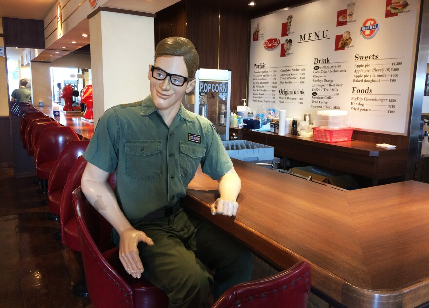 A replica of an American serviceman that sits at the counter of the diner-like Blue Seal ice cream shop.