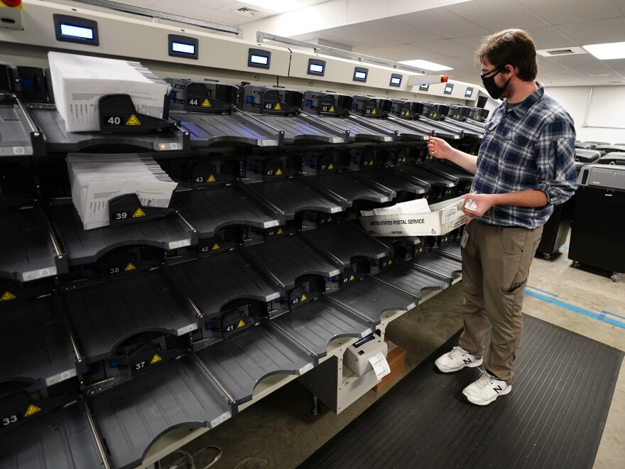 An election official gathers mail-in ballots being sorted in Chester County, Pennsylvania.