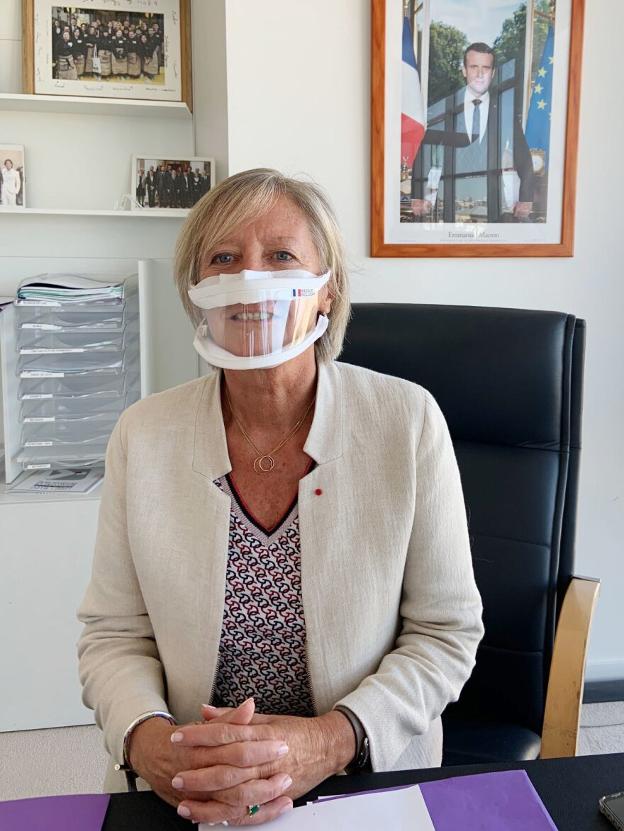 Sophie Cluzel, France's secretary of state in charge of disability issues, demonstrates a transparent mask in her office.