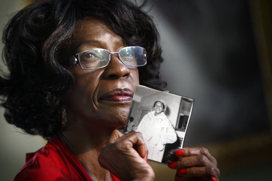Mamie Pinder holds a photograph of herself as a young teaching student. Pinder, a retired Miami-Dade school teacher, began teaching in 1963, the year the school district began merging black and white students bodies and faculty.