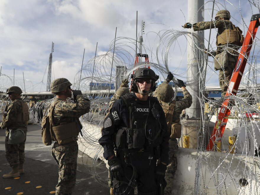 Troops set up concertina wire as a Customs and Border Protection agent stands guard on the U.S. side of the border with Mexico, on Thanksgiving Day.
