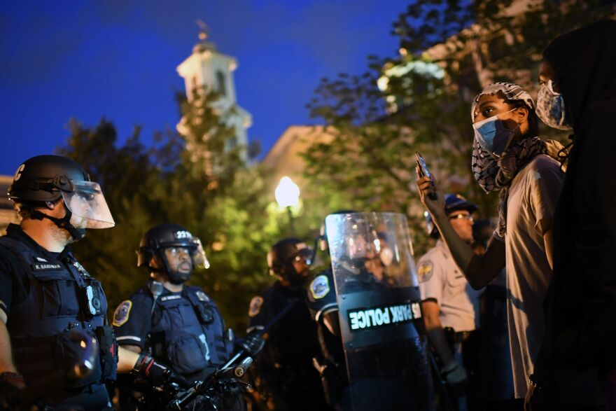 Protesters confront a row of police officers at Lafayette Square in front of the White House on Monday night. Protesters removed a chain-link fence that had recently been placed around the statue and climbed its base to tie ropes around the neck of Jackson and his horse, according to The Associated Press. Efforts to pull the statue off its pedestal were unsuccessful.
