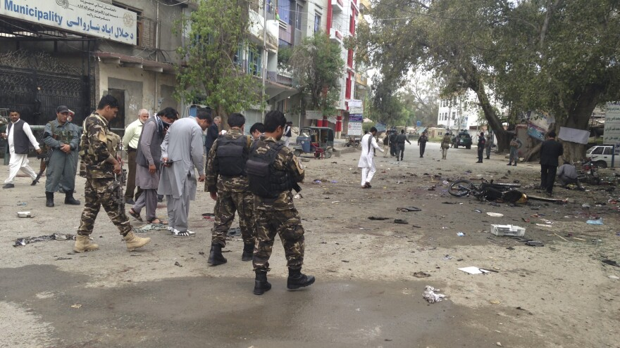 Afghan security forced inspect the site of a suicide attack near a New Kabul Bank in Jalalabad in eastern Afghanistan Saturday. The United Nations says at least 35 people died.