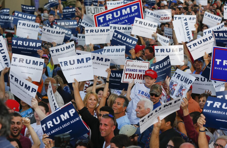 Audience members hold up signs supporting Republican presidential candidate Donald Trump during a campaign rally in Boca Raton, Fla., on Sunday.
