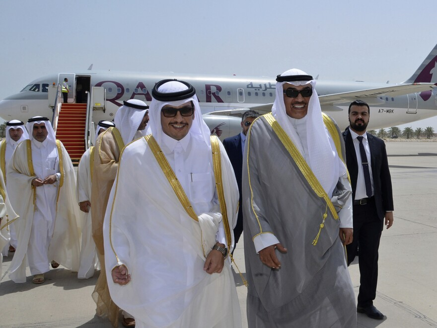 Qatari Foreign Minister Sheikh Mohammed bin Abdulrahman Al Thani, left, and Kuwaiti Foreign Minister Sheikh Sabah Khaled Al Sabah, right, walk together on an airport tarmac in Kuwait. Qatar's foreign minister delivered a letter from his country's ruling emir amid a diplomatic crisis engulfing his nation.