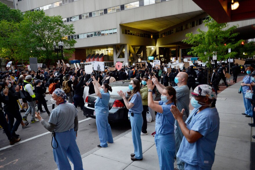 Medical workers applaud protesters outside a hospital in Boston on Sunday during a demonstration over the death of George Floyd.