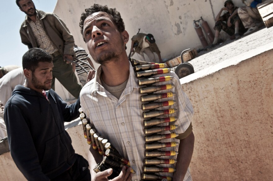 A Libyan rebel carries heavy machine gun rounds captured from a weapons depot, part of a network of bunkers belonging to Moammar Gadhafi.