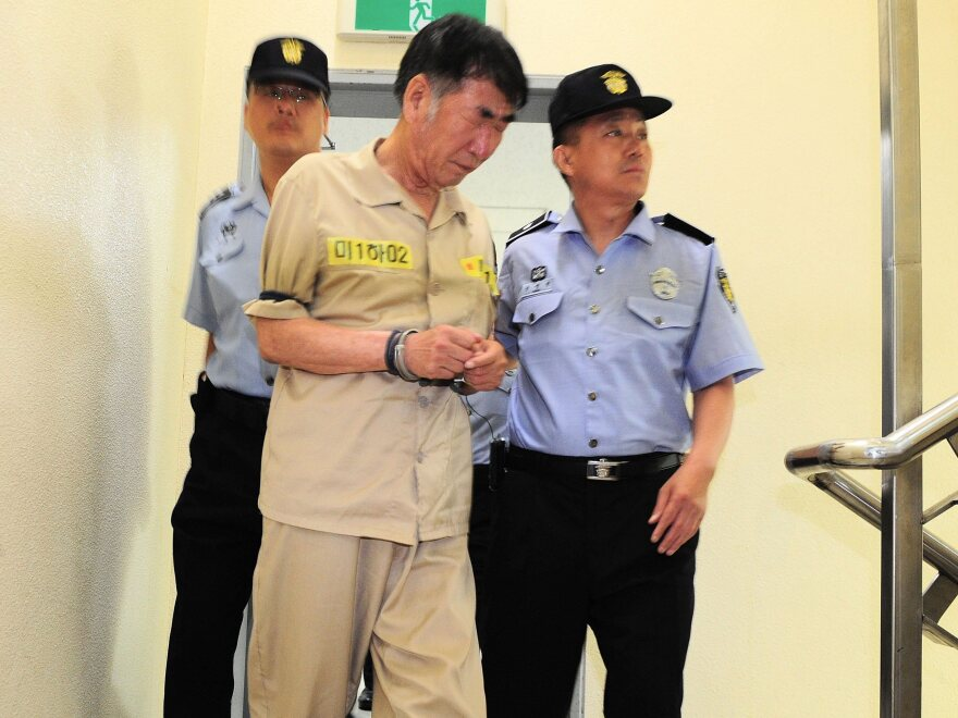 The captain of the sunken ferry Sewol, Lee Joon-Seok (left) arrives on the second day of his trial at the Gwangju District Court in Gwanju, southwestern South Korea, in June.