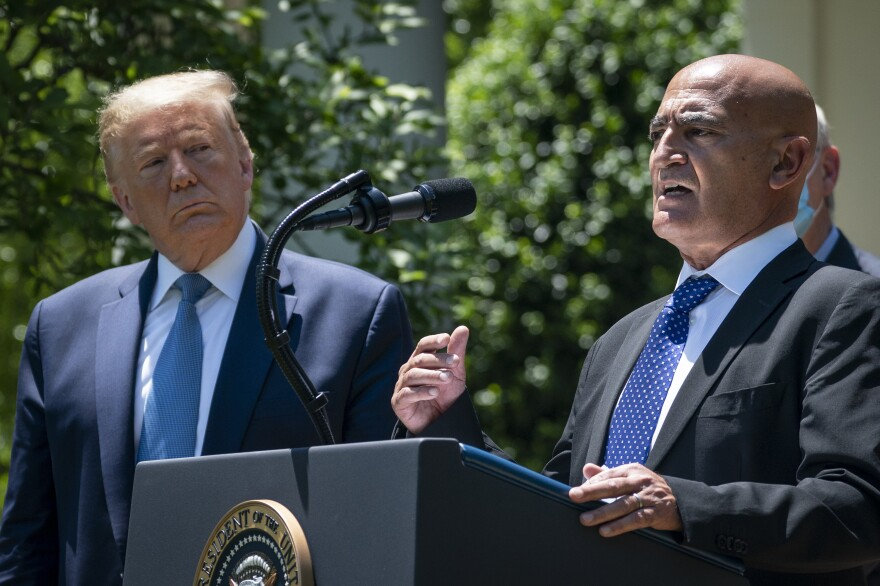 President Trump listens as Moncef Slaoui, the former head of GlaxoSmithKlines vaccines division, speaks about coronavirus vaccine development on May 15.