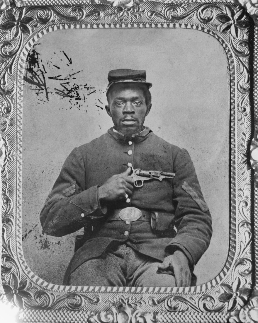 Negro Union Infantry corporal, holding a Colt model 1849 pocket revolver.