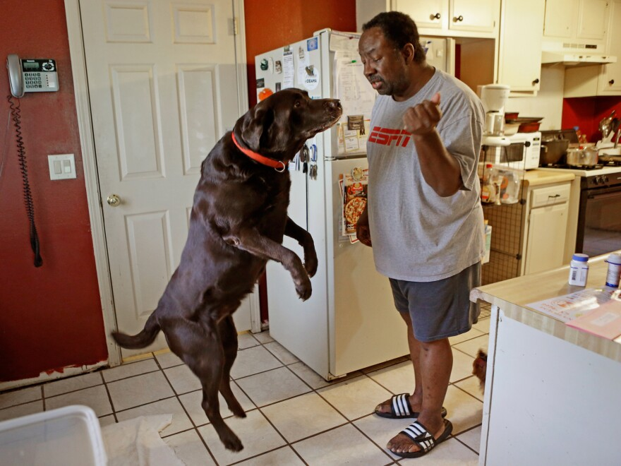"Mike Jackson and his dog Coco at home in Oklahoma City. He says of his medical costs: ""If anything goes wrong, I'm one step away from disaster."""