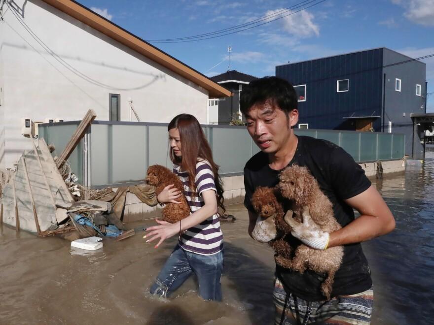 Residents flee a flooded area in Kurashiki, Okayama prefecture, on Sunday. Heavy rains have devastated central and western Japan.