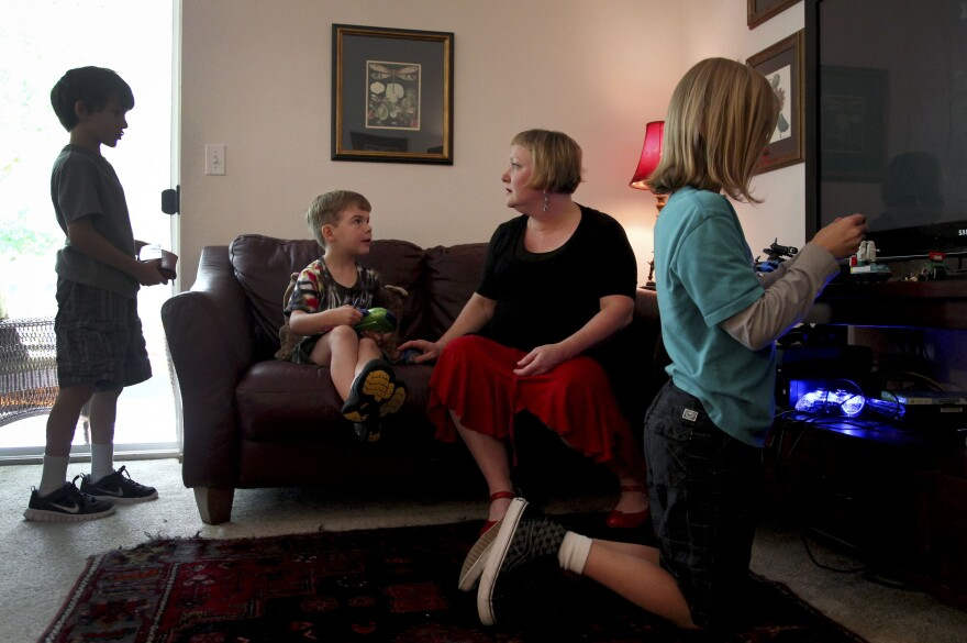Moritz plays with her sons (from left) Elliot, 8, Ariel, 6, and Aidan in their apartment. The children also have had health problems since their father's accident.