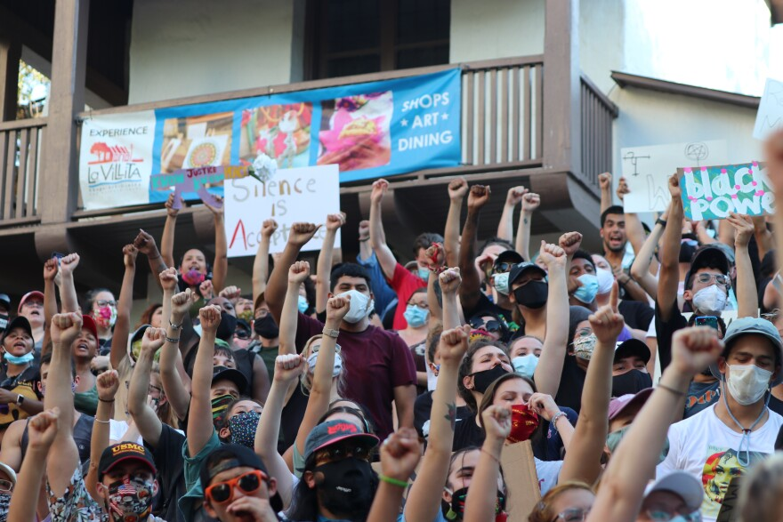 Protesters raise their fist in solidarity with Black people in San Antonio and in the nation at a protest on June 8, 2020.