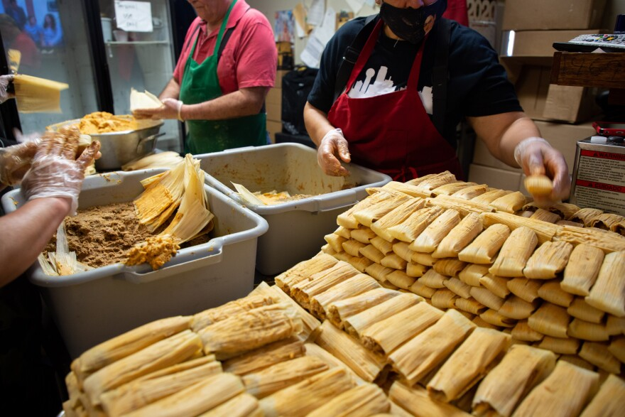 The tamale crew consists of two people who spread the dough on the corn husk, and two others who fill it with meat or chicken, before folding it together. A batch of tamales is piling up in the right corner. There are Tupperware filled with dough and meat.