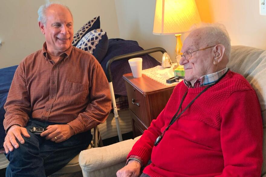 Gene Popiolek (l) and his father Bernie sit in an assisted living facility bedroom.