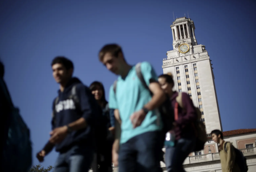 UT Austin students pass by the main building on campus on their way to and from classes.