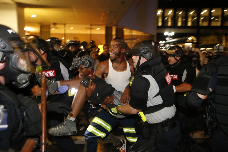 Police and protesters carry a seriously wounded protester into the parking area of the the Omni Hotel during a march on Wednesday in Charlotte, N.C. The shooting victim died Thursday. Police say the protester was shot by another civilian, while many protesters blamed police for the shooting. After the shooting, the uptown protest turned into hours of violence and destruction.