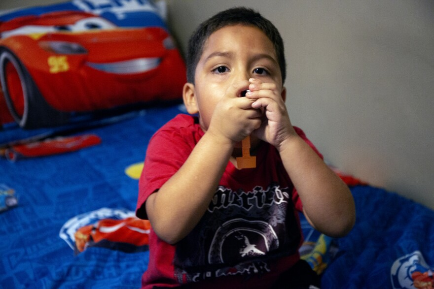 A little boy sits on his twin bed with both hands gripped around an inhaler.
