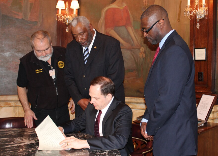 St. Louis Mayor Francis Slay (center) signs into law the Veterans Preference Bill, giving veterans extra points on applications for city jobs. The bill was sponsored by 22nd Ward Alderman Jeffrey Boyd (right).